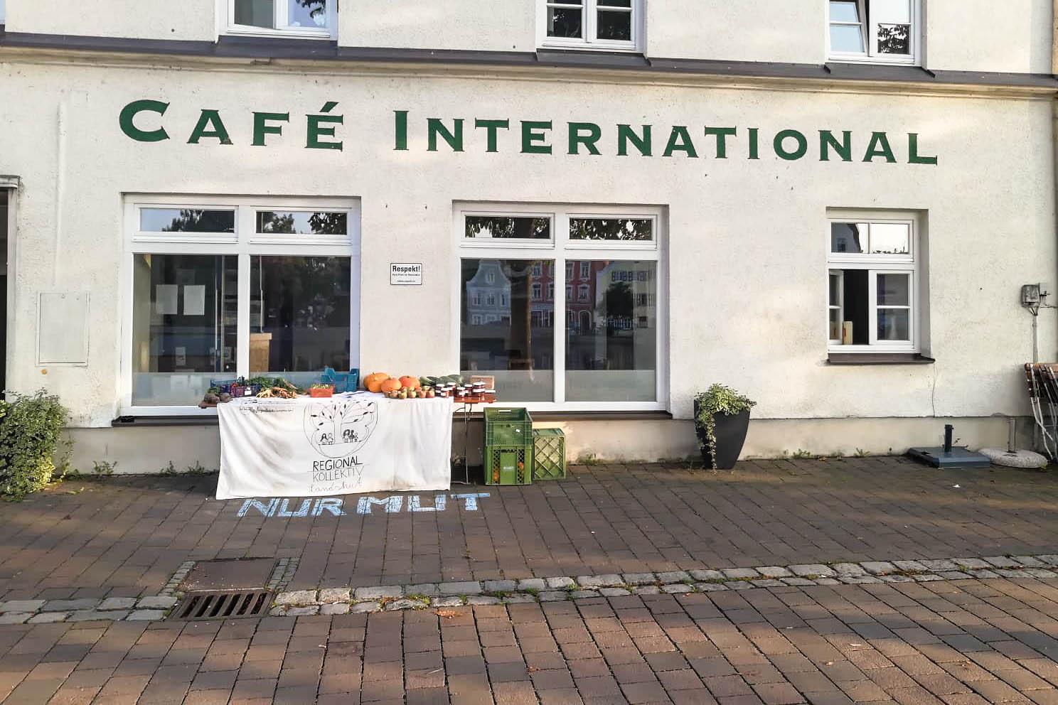 """Hausfront mit dem Café International, vor den Fenstern des Cafés ein Tisch mit Gemüse und einem Banner """"Regionalkollektiv"""""""